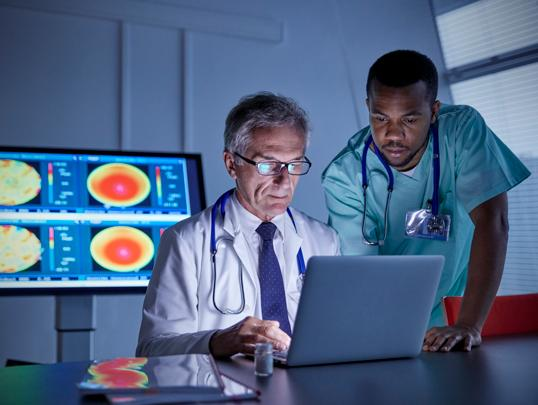 Doctors reviewing charts on laptop